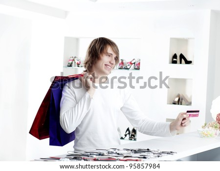 Young man at shopping mall checkout counter paying through credit card