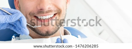 Young man at the dentist. Dental care, taking care of teeth. Picture with copy space for background.