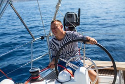 Young man at the helm sail boat, the ship controls during sea yacht race.