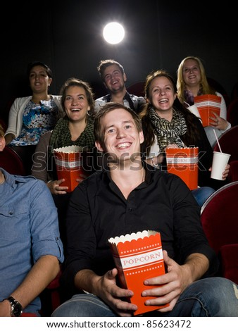 Young man at the movie theater with bag of popcorn