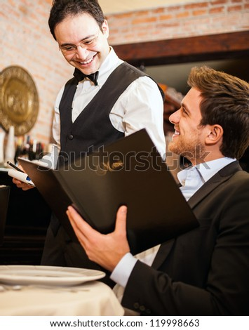 Young man at the restaurant ordering meal to a waiter