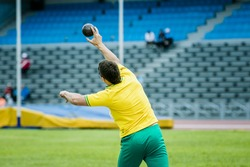 young man athlete shot put competitions in summer at stadium. view from back