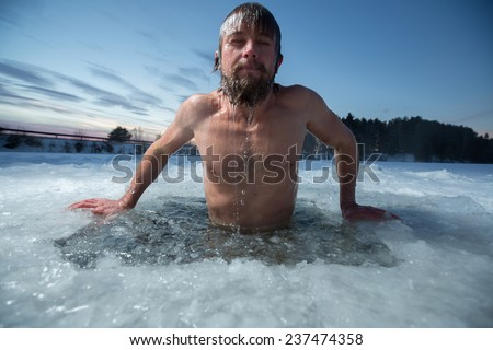 Young man bathing in the ice hole #237474358