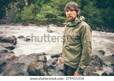 Young Man bearded hiking outdoor with river and forest wild on background Lifestyle Travel survival concept