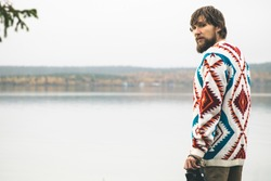 Young Man bearded with retro photo camera Fashion Travel Lifestyle wearing knitted sweater clothing outdoor foggy nature on background