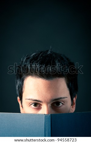 Young man behind a book on dark background.