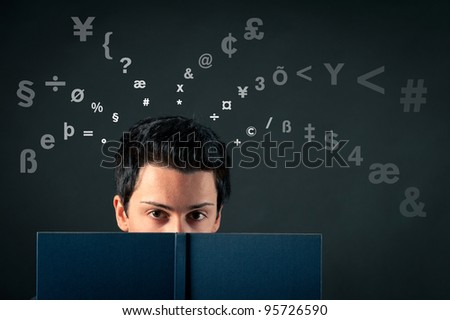 Young man behind a book with letters coming out of his head against dark background.