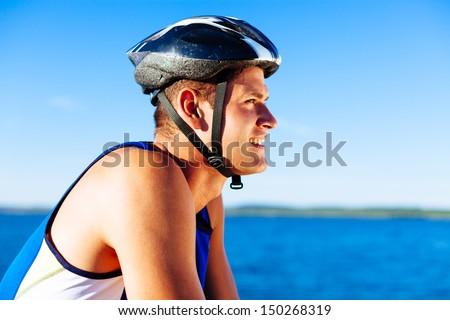 Young man biking with helmet on head