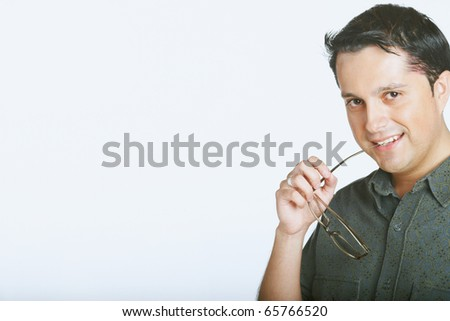 Young man biting the ends of his glasses