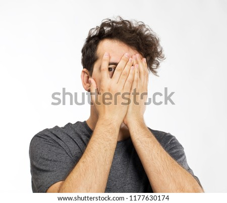 Young man blocking face with hands #1177630174