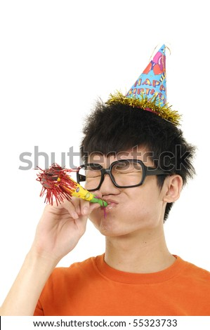 Young man blowing a Party Favor and Wearing a Party Hat
