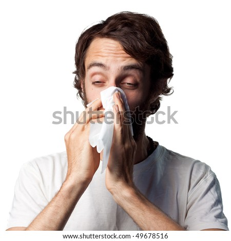 Young man blowing his nose