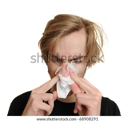 Young man blowing his nose because he is very ill and sick with a cold and fever. Isolated on white background.