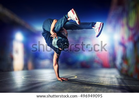 Young man break dancing at night on urban painted walls background ストックフォト ©