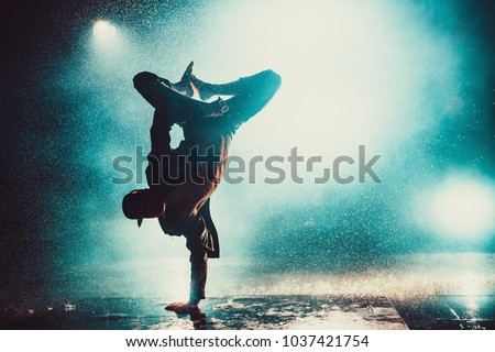 Young man break dancing in club with lights and water. Blue dramatic colors. #1037421754