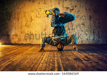 Young man break dancing on wall background. Vibrant blue and red colors effect. #564086569