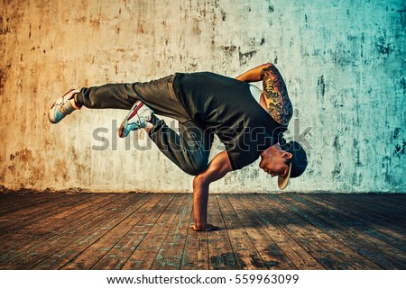 Young man break dancing on wall background. Vibrant colors effect. Tattoo on body. ストックフォト ©