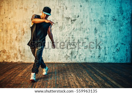 Young man break dancing on wall background. Vibrant colors effect. Tattoo on body.