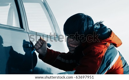 Young man breaking door of a car