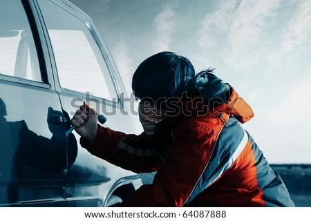 Young man breaking door of a car