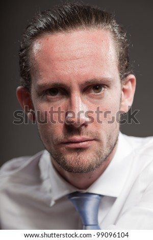 Young man brown hair wearing white shirt and blue tie showing emotions. Isolated on grey background. #99096104