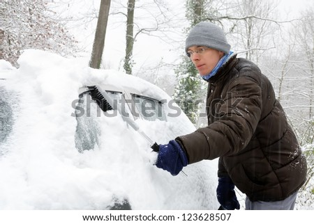 Young man brushing the snow off his car on a cold winter day