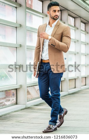 Young Man Business Casual Fashion in New York, with beard, wearing brown blazer, white shirt, blue pant, black leather shoes, wristwatch, holding laptop computer, standing inside indoor walkway.