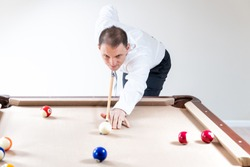 Young man, businessman in tie and white shirt holding cue by pool table, playing game of billiard by striking white ball