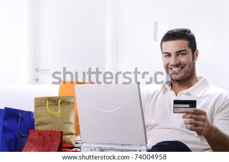young man buying on internet with laptop in indoor