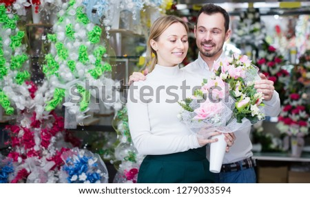 Young man buys a bouquet of flowers to a girl in a flower shop