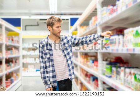 young man buys juices and milk for home