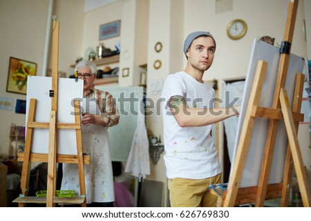 Young man by easel drawing from life in workroom