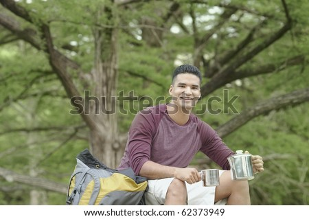 Young man camping in a forest