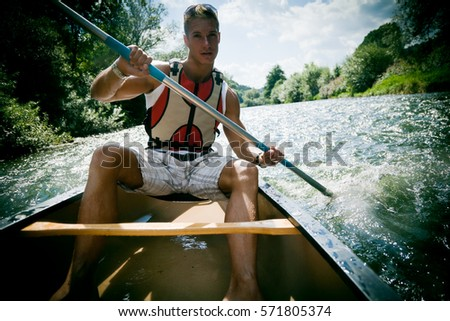 Young Man Canoeing #571805374