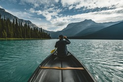 Young Man Canoeing on Emerald Lake in the rocky mountains canada with canoe and mountains in the background blue water.