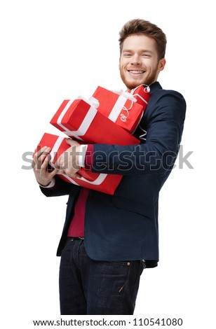 Young man carries a lot of presents, isolated on white