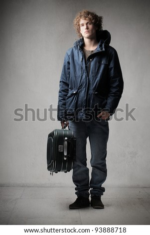 Young man carrying a trolley case