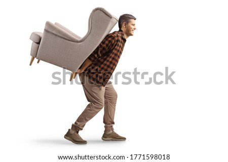 Young man carrying an armchair on his back isolated on white background ストックフォト ©