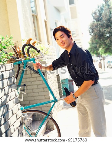 Young man carrying bicycle - stock photo