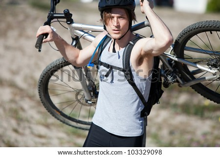 Young man carrying his mountain bike - stock photo