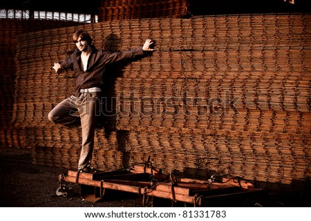 young man casual in shirt and pants, lean on rusty wire armature