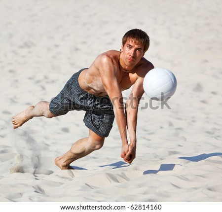 Young man catching ball in volleyball game.