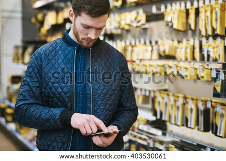 Young man checking a text message on his mobile phone as he shops in a hardware store store for DIY supplies