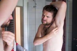 Young man checking his lymph node under armpit being worried about cancer at bathroom.