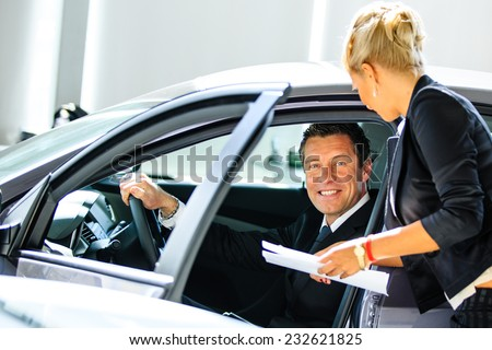 Young man choosing car at salon with help of consultant