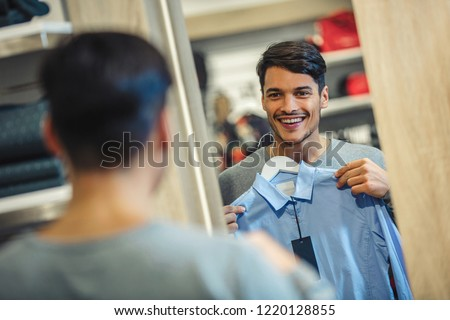 Young man choosing shirt and looking to mirror in mall or clothing store