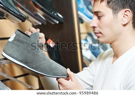 Young man choosing shoes during footwear shopping at shoe shop