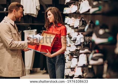 Young man choosing sneakers at sportswear shop ストックフォト ©