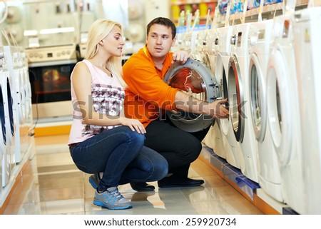 Young man choosing washing machine in home appliance shopping mall supermarket