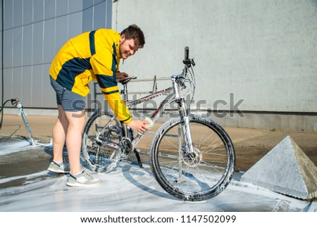 young man clean bicycle with soap and sponge at carwash self-service. lifestyle